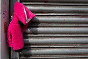 A dropped pink child's coat hanging from a closed shop's shutters on the Walworth Road in south London, on 21st August 2019, in London, England.