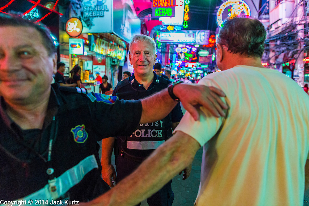 "26 SEPTEMBER 2014 - PATTAYA, CHONBURI, THAILAND: Members of the Foreign Tourist Police Assistants (FTPA) talk to an Italian tourist on Walking Street in Pataya. The FTPA assist local police in dealing with foreign tourists but don't have arrest powers. Pataya, a beach resort about two hours from Bangkok, has wrestled with a reputation of having a high crime rate and being a haven for sex tourism. After the coup in May, the military government cracked down on other Thai beach resorts, notably Phuket and Hua Hin, putting military officers in charge of law enforcement and cleaning up unlicensed businesses that encroached on beaches. Pattaya city officials have launched their own crackdown and clean up in order to prevent a military crackdown. City officials have vowed to remake Pattaya as a ""family friendly"" destination. City police and tourist police now patrol ""Walking Street,"" Pattaya's notorious red light district, and officials are cracking down on unlicensed businesses on the beach.     PHOTO BY JACK KURTZ"