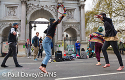 Activists dance in front of Marble Arch as hundreds of environmental protesters from Extinction Rebellion occupy Marble Arch, camping in the square and even on the streets, blocking access to traffic on Park Lane and Oxford Street in London's usually traffic-heavy west end. . London, April 16 2019.
