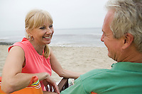 Middle-aged couple sitting on beach
