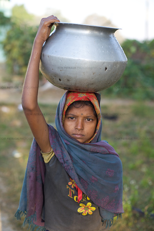 A young woman collects water at a water pump in the Adivasi (tribal) village of Kanbhita in Ranchi district. UNICEF, through partners Mahila Samakhya, work to encourage hygiene and good health practices among the women and children of Kanbhita .<br /> <br /> Mahila Samakhya is UNICEF's partner in eleven districts in Jharkhand. Mahila Samakhya work with Adivasi (tribal) communities in Ranchi district, encouraging good hygiene practices including handwashing and providing practical support for the construction of latrines in an area where two thirds of the population defecate in the open. Mahila Samkhya work with women's self help groups to encourage good waste water management and provide advise on wormi composting. Mahila Samakhya also work in schools and child residential centres, promoting hygiene and sanitation through staff training and the distribution of learning materials. UNICEF are advisors and technical assistants to the Jharkhand government in the implementation of the government's Total Sanitation Campaign (TSC). <br /> <br /> Photo: Tom Pietrasik<br /> Ranchi District, Jharkhand, India<br /> October 29th 2009