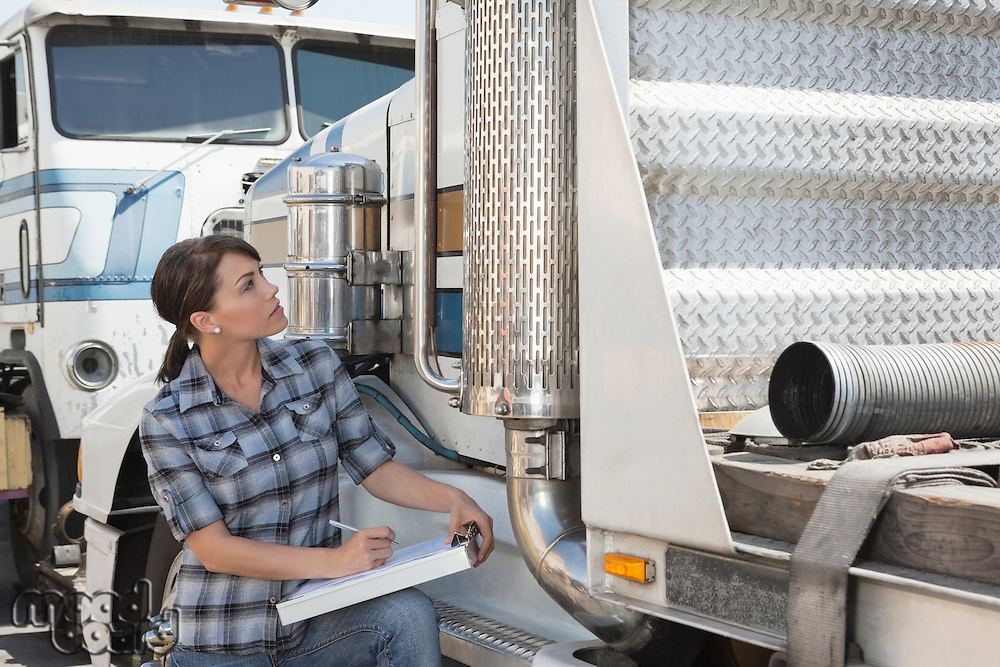 Woman inspecting flatbed truck