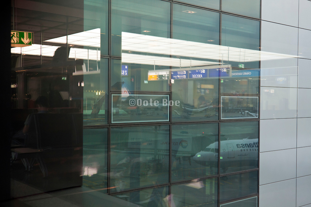 departure terminal and airplane reflecting in window at Frankfurt airport Germany