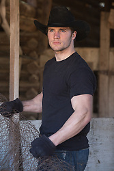 sexy cowboy in a black tee shirt working on a ranch