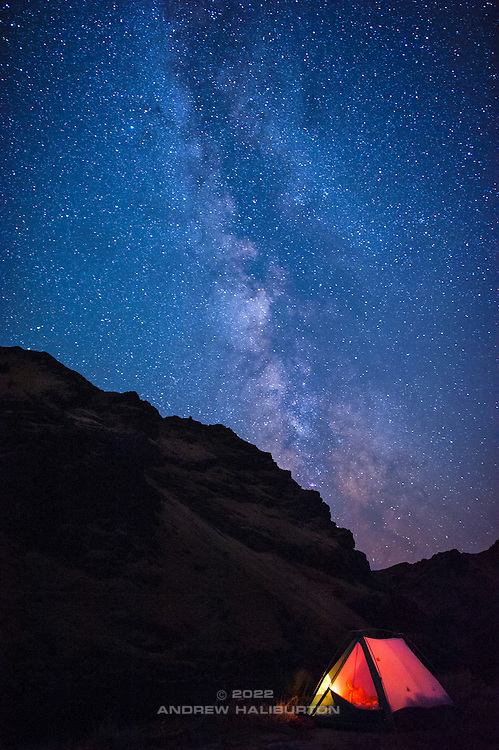 The Milky Way appears to rise like smoke across the starry night sky from our glowing tent on the banks of the Snake River in the mighty Hell's Canyon, Oregon. Nikon D700. Bower MF 24mm f/1.4.