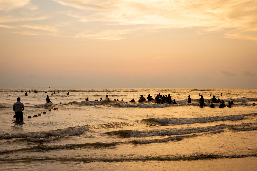 Groups of people swimming in the Bay of Bengal sea during sunset on Laboni Beach, Cox Bazar, Chittagong Division, Bangladesh, Asia. The sun is setting behind clouds in the sky and the horizon is warm with an orange glow.  (photo by Andrew Aitchison / In pictures via Getty Images)