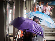 "16 SEPTEMBER 2015 - BANGKOK, THAILAND:  People with umbrellas leave the Phaya Thai BTS Station in Bangkok during a rainstorm. The remnants of tropical storm ""Vamco"" hit Bangkok Wednesday. The storm, downgraded to a tropical depression, brought bands of rain to central Thailand, including Bangkok. The Thai Meteorological Department said the storm would help alleviate the drought that has gripped Thailand since late last year.     PHOTO BY JACK KURTZ"