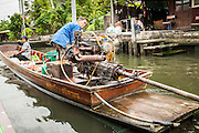 "17 NOVEMBER 2012 - BANGKOK, THAILAND:  A couple on their ""long tailed"" boat in Bangkok. Long tailed boats use big V8 car engines and have 30-40 foot long propeller shafts that extend past the back of the boat. Bangkok used to be known as the ""Venice of the East"" because of the number of waterways the criss crossed the city. Now most of the waterways have been filled in but boats and ships still play an important role in daily life in Bangkok. Thousands of people commute to work daily on the Chao Phraya Express Boats and fast boats that ply Khlong Saen Saeb or use boats to get around on the canals on the Thonburi side of the river. Boats are used to haul commodities through the city to deep water ports for export.    PHOTO BY JACK KURTZ"