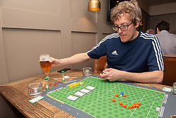Edinburgh football fan and game designer Colin Webster has designed a brand-new football strategy game called Counter Attack. Last night he hosted a game session in Leith to demonstrate the game to a few interested players. The game is currently on the crowd-funding site Kickstarter and on track to meet it's funding target. If so, Colin hopes the gamne will be available by August this year. Pictured: Colin explains the rules of his new game<br /> <br /> <br /> &copy; Jon Davey/ EEm