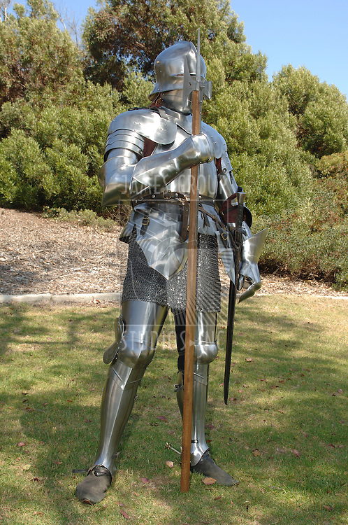 15th Century English knight in shining armour standing outside with battle axe