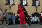Hooded penitents carry wooden crosses as they begin the Procession of Silence through the streets on Good Friday during Holy Week March 30, 2018 in Querétaro, Mexico. The penitents, known as Nazarenes, carry the heavy crosses and drag chains in a four hour march in memory of the passion of Christ.