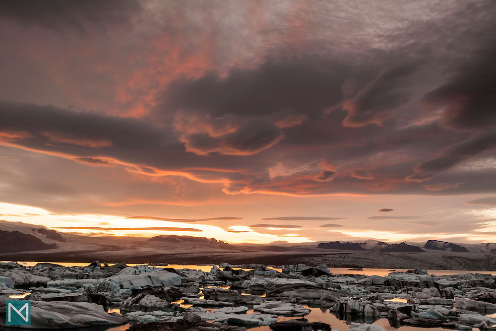 The long sunset over Jökulsárlón glacier lagoon in south east Iceland paints the clouds bright orange