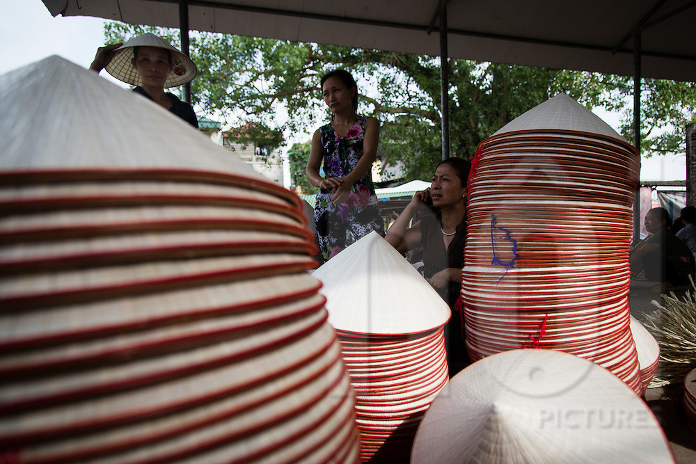 """Stacks of conical hats in Chuong Village, Ha Tay Province, Vietnam, Southeast Asia, 2013. This handicraft village specializes in the fabrication of the conical hat, known as """"non"""" in Vietnamese."""