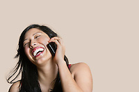 Cheerful young woman talking on mobile phone over colored background