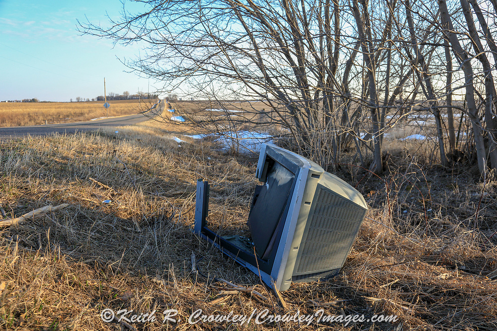 Broken Television discarded on the side of a country road.