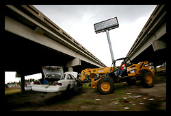 19 June, 2006. New Orleans, Louisiana. Towing junk cars. Finally, 10 months after hurricane Katrina, one of the enduring symbols of the storm, thousands of flooded cars now little more than junk are being towed away by private contractors. The cars will be crushed and sold for recycled metal.