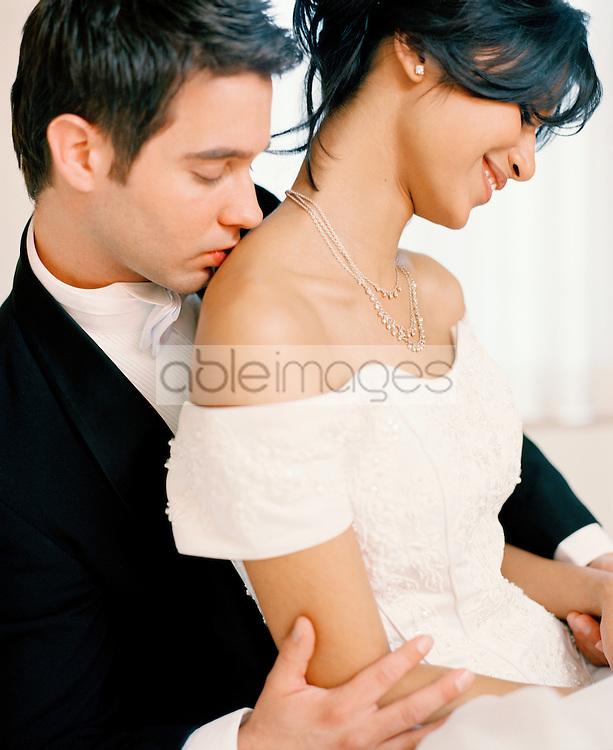 Close up of a bridegroom kissing a bride shoulder