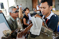 Staff of Bali Eye assessing a patient's sight prior to issuing free corrective glasses, Bali, Indonesia.