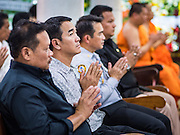 20 AUGUST 2015  - BANGKOK, THAILAND: Men pray at the funeral for Yutnarong Singraw Thursday. More than 100 people gathered at Wat Bang Na Nok in Bangkok for the third day of the funeral rites for  Yutnarong Singraw, a Thai man who was killed in the bombing at the Erawan Shrine in Bangkok Monday. Yutnarong was delivering legal documents when the blast occurred. More than 20 people were killed and more than 100 injured in the blast.    PHOTO BY JACK KURTZ