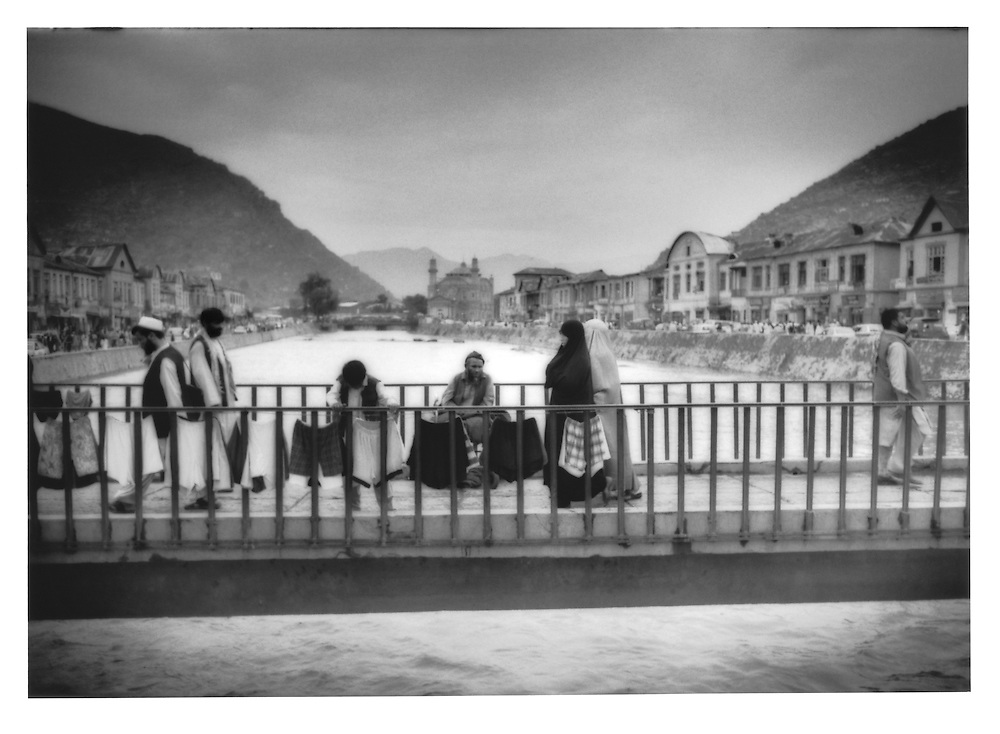 Sellers and passersby on bridge over rain-swollen Kabul River, Afghanistan.