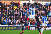 Juninho Bacuna of Huddersfield Town (7) heads on above Shkodran Mustafi of Arsenal (20) during the Premier League match between Huddersfield Town and Arsenal at the John Smiths Stadium, Huddersfield, England on 9 February 2019.