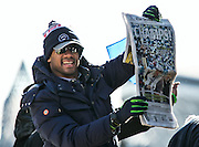 Seahawks quarterback Russell Wilson holds up a copy of The Seattle Times featuring the Super Bowl XLVIII winners for the crowd to see, during the Seahawks Super Bowl parade along 4th avenue in downtown Seattle, on Wednesday, Feb. 5, 2014.<br />