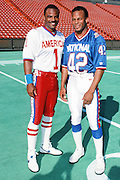 American Football Conference Houston Oilers quarterback (1) poses for a photo with National Football Conference San Francisco 49ers safety Ronnie Lott (42) at photo day during the week before the 1989 NFL Pro Bowl football game against the National Football Conference on Jan. 24, 1989 in Honolulu. The NFC won the game 34-3. (©Paul Anthony Spinelli)