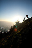 One person helping another up a steep section of trail while hiking on Neahkahnie Mountain near Manzanita, Oregon.