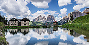 A pond reflects Hotel Gonzaga and peaks of the Langkofel Group (Sassolungo, 3181 meters / 10,436 feet) and Sella Group, in Val di Fassa, 2 km west of Passo Pordoi, in the Dolomites, Trentino-Alto Adige/Südtirol region, Italy. We highly recommend lodging in a pristine, roomy apartment with full kitchen in a beautiful setting at Hotel Gonzaga Appartamenti Garni (Canazei, I-38032, Streda de Pordoi, 102, telephone +39 0462 602121). The Dolomites are part of the Southern Limestone Alps, Europe. UNESCO honored the Dolomites as a natural World Heritage Site in 2009. This panorama was stitched from 2 overlapping photos.