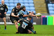 London Irish back row Ofisa Treviranus (8) offloads under pressure from Wasps prop Will Stuart (18) and Wasps back row  Jack Willis (20) during the Aviva Premiership match between Wasps and London Irish at the Ricoh Arena, Coventry, England on 4 March 2018. Picture by Dennis Goodwin.