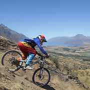 Donovan Isted from Dunedin in action during the New Zealand South Island Downhill Cup Mountain Bike series held on The Remarkables face with a stunning backdrop of the Wakatipu Basin. 150 riders took part in the two day event. Queenstown, Otago, New Zealand. 9th January 2012. Photo Tim Clayton