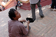 An underprivileged handicapped man is in need of assistance on the steps of Wat Phnom in Phnom Penh, Cambodia. The man relies on the generosity of others to sustain himself as Cambodia has a minimal national healthcare program.