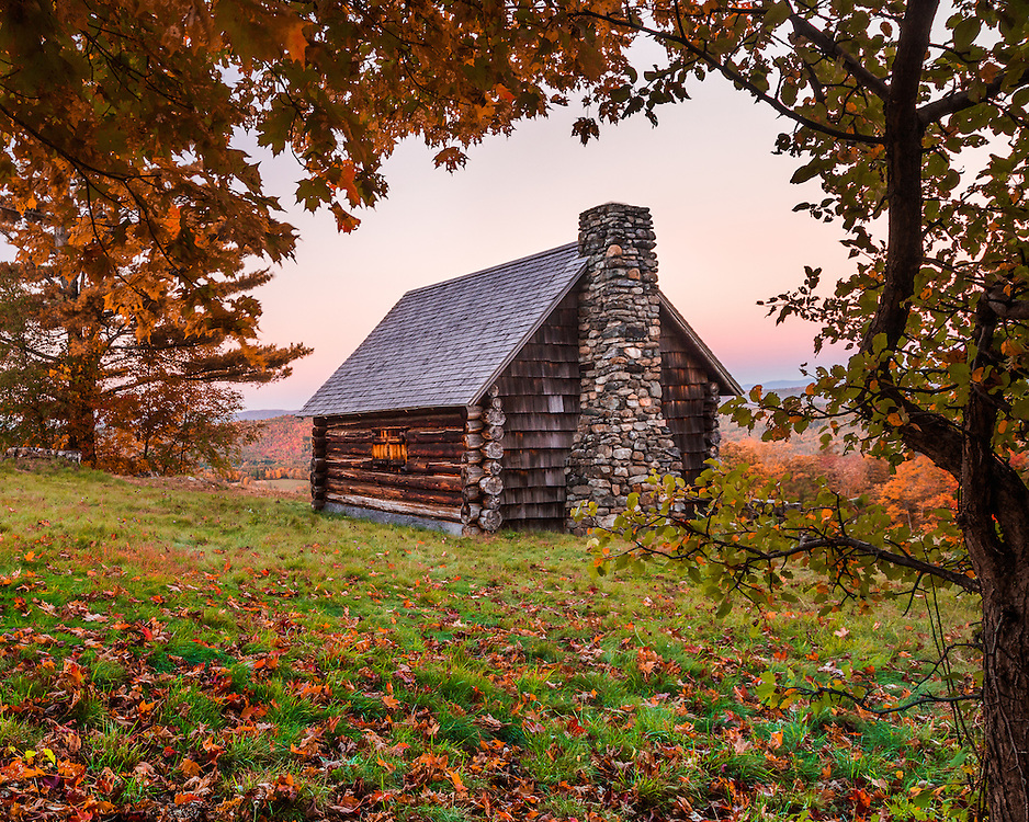 A log cabin with a fieldstone chimney nestles on a hillside surrounded by beautiful fall colors in Sugar Hill New Hampshire.