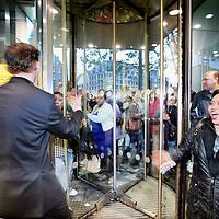 """Nederland, Amsterdam , 1 oktober 2009..Het publiek wacht buiten in de regen op het moment dat de deuren van de Bijenkorf opengaan  voor de koopjes tijdens de eerste dag  van de Drie Dwaze Dagen ..Op de foto """"het"""" moment.De deuren gaan open en mensen stormen naar binnen..Three Crazy Days, annual sale of the Bijenkorf store, promoting bargains."""