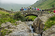 Stockley Bridge over River Derwent in Borrowdale valley, Lake District National Park, United Kingdom, Europe. England Coast to Coast hike with Wilderness Travel, day 3 of 14: from Wasdale Head to Seathwaite. From Wasdale Head, we climbed to 1637-foot Styhead Pass, then descended via Styhead Tarn to the valley of Borrowdale. Overnight at Keswick Country House, in Cumbria county. [This image, commissioned by Wilderness Travel, is not available to any other agency providing group travel in the UK, but may otherwise be licensable from Tom Dempsey – please inquire at PhotoSeek.com.]