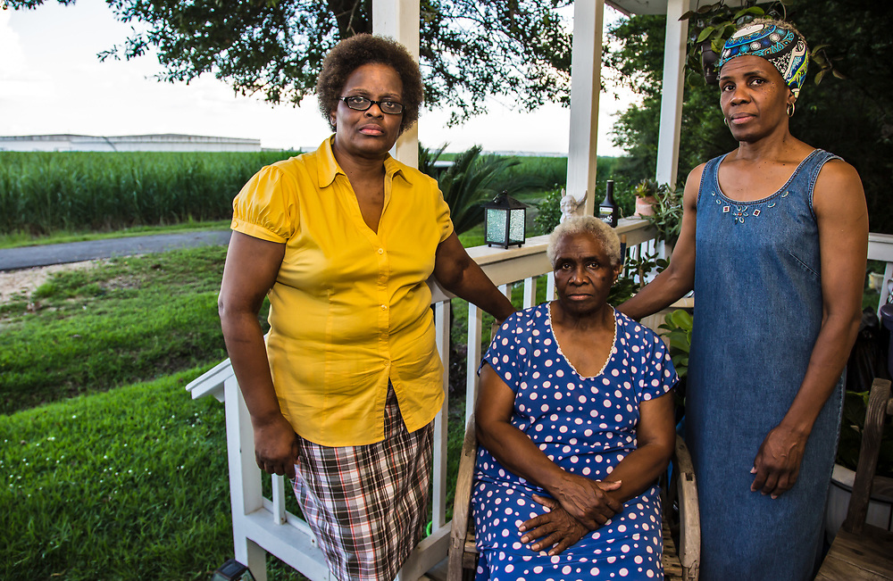 Eve Miller  with her mother and sister on her front porch in St. James, across from oil storage tanks.