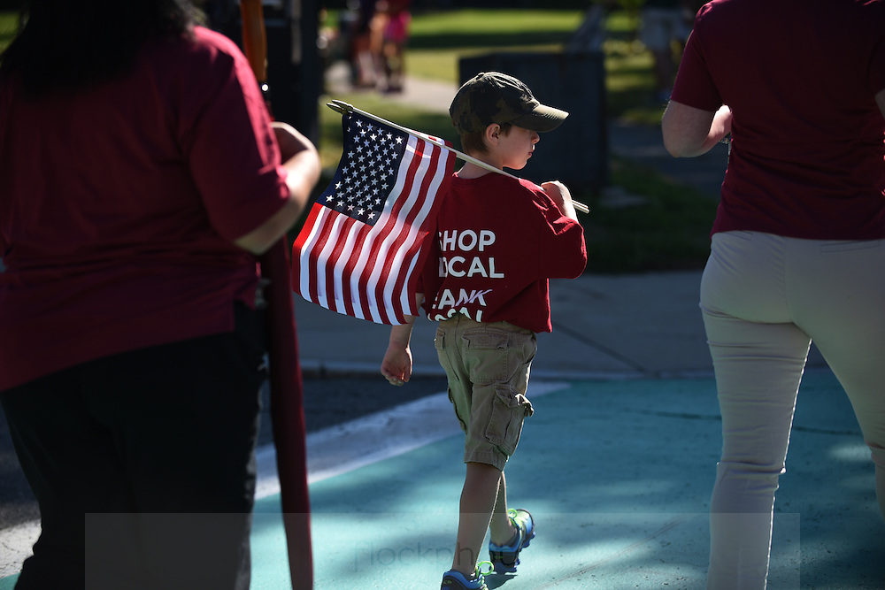 A boy carries an American flag on the way to Needham's annual Grand Parade on July 4, 2016.<br /> Wicked Local staff photo / Kate Flock