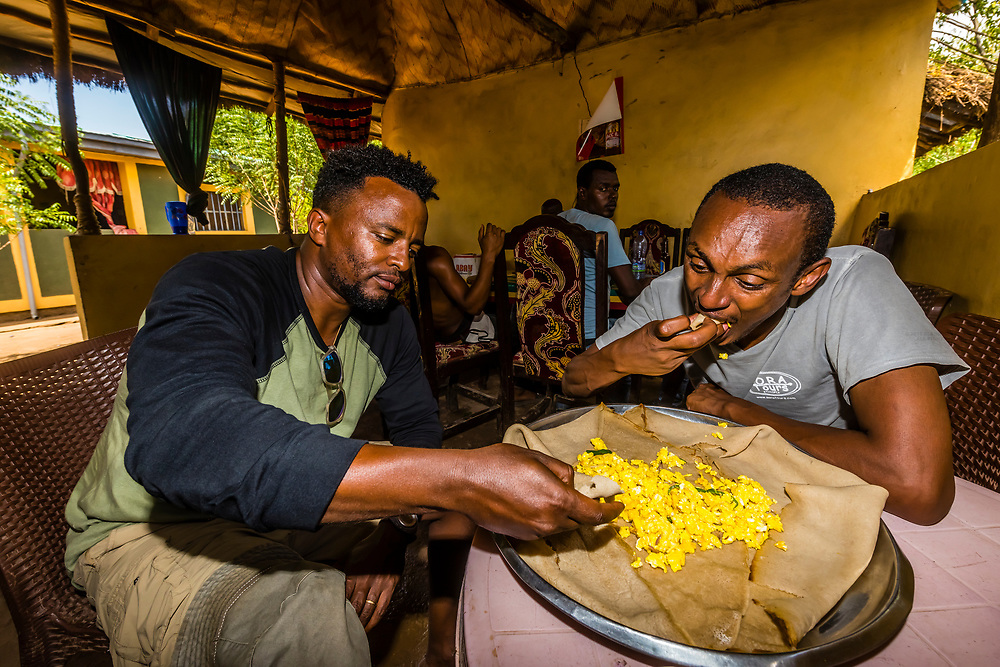 Men eating injera, the national dish of Ethiopia. It is a sourdough-risen flatbread with slightly spongy texture, traditionally made out of teff flour.