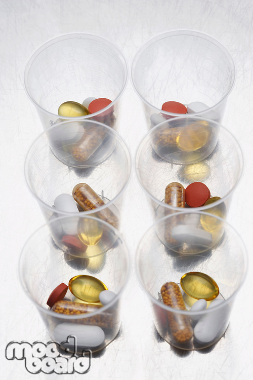 Pills and tablets in six plastic cups