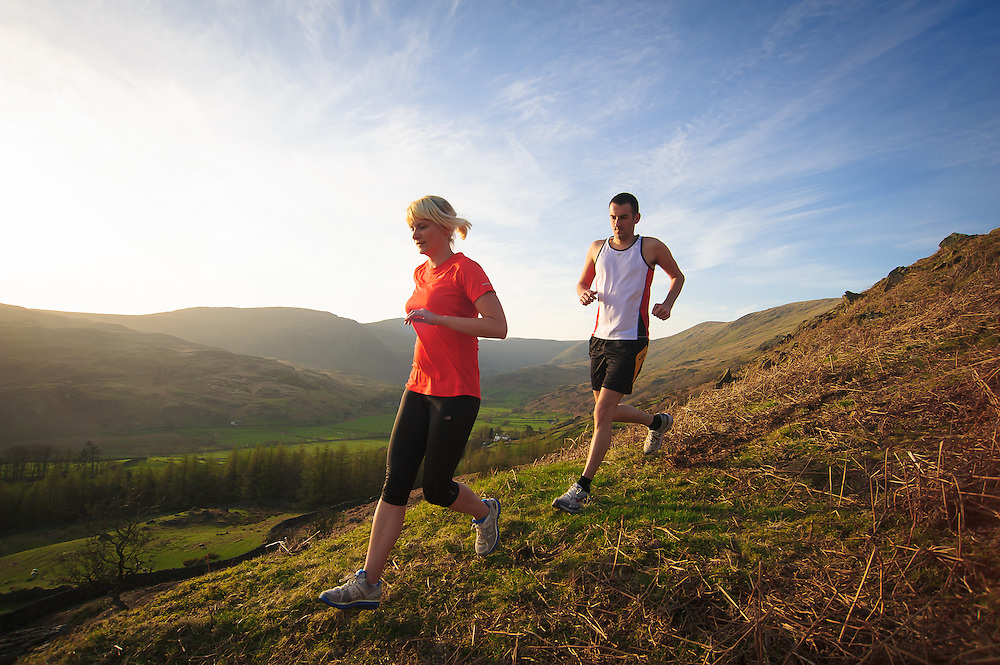 A male and female runner at Kentdale in the Lake District, evening sunshine, summer,Cumbria, UK