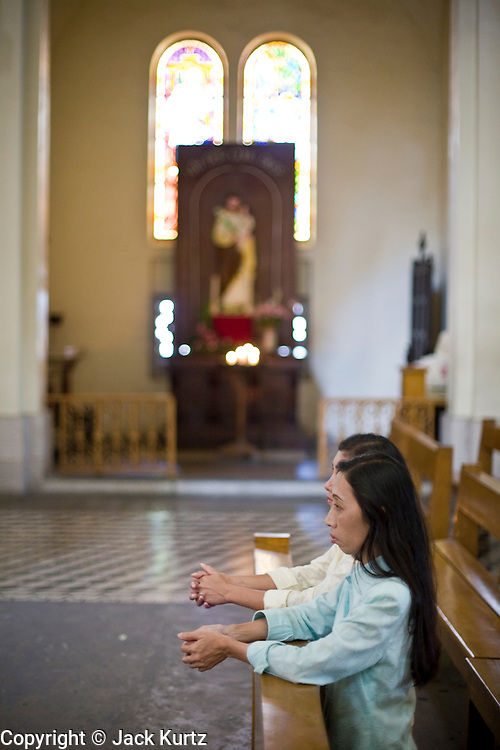 09 MARCH 2006 - HO CHI MINH CITY, VIETNAM: Women pray in Notre Dame Cathedral in Ho Chi Minh City (Saigon), Vietnam. Vietnam has the second largest population of Catholics in southeast Asia. Religion was barely tolerated for years by the communist government but as more tourists flock to Vietnam and the economy has flourished, restrictions on the practice of religion have been loosened.    PHOTO BY JACK KURTZ
