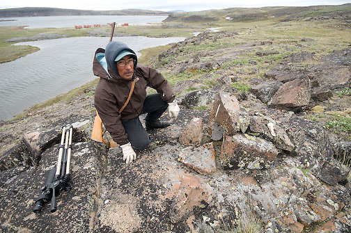 Peter Kapolak inspects an ancient fox trap made form rocks near Elu Lodge, most likely made by the Copper Inuit, Nunavut, Canada