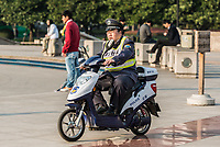 Shanghai, China - April 7, 2013: policeman patrolling with electric motorcycle on people's square at the city of Shanghai in China on april 7th, 2013