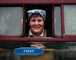 © Licensed to London News Pictures. <br /> 16/10/2016. <br /> Grosmont, UK.  <br /> <br /> A woman wearing 1940's Land Army clothing poses for a picture from the train at Grosmont station during the final day of the North Yorkshire Moors Railway Wartime Weekend event. <br /> The annual event brings together re-enactors and enthusiasts along the length of the NYMR heritage steam railway line to recreate the feel of the war years of the 1940's. <br /> <br /> Photo credit: Ian Forsyth/LNP
