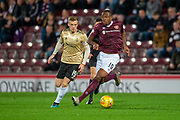 Uche Ikpeazu (#19) of Heart of Midlothian FC runs past  Lewis Ferguson (#19) of Aberdeen FC during the Betfred Scottish Football League Cup quarter final match between Heart of Midlothian FC and Aberdeen FC at Tynecastle Stadium, Edinburgh, Scotland on 25 September 2019.