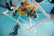 A pilot for Cal Fire goes into the pool during a training exercise for helicopter evacuation in case of a crash landing in water at the C.H.P. Academy pool, Friday April 15, 2011.
