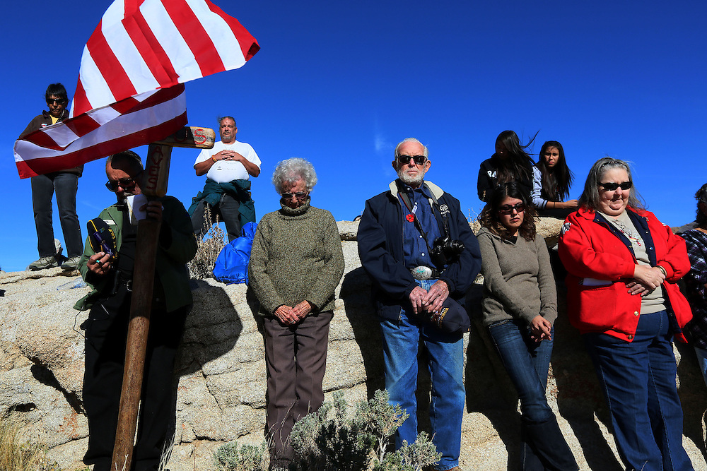 Veterans and supporters bow their heads in prayer during an unveiling ceremony for the Mojave Cross on Veterans Day in Cima, California on Sunday, November 11, 2012.  A battle has been brewing for over Thirteen years over whether the cross can legally stay on Sunrise Rock because it violates Separation of Church and State and is in the Mojave National Perserve which is on Federal Lands.  The Veterans of Foreign Wars and American Legion Society raised money to purchase the plot of land and has kept the cross in place and today serves as war memorial.(Photo by Sandy Huffaker)