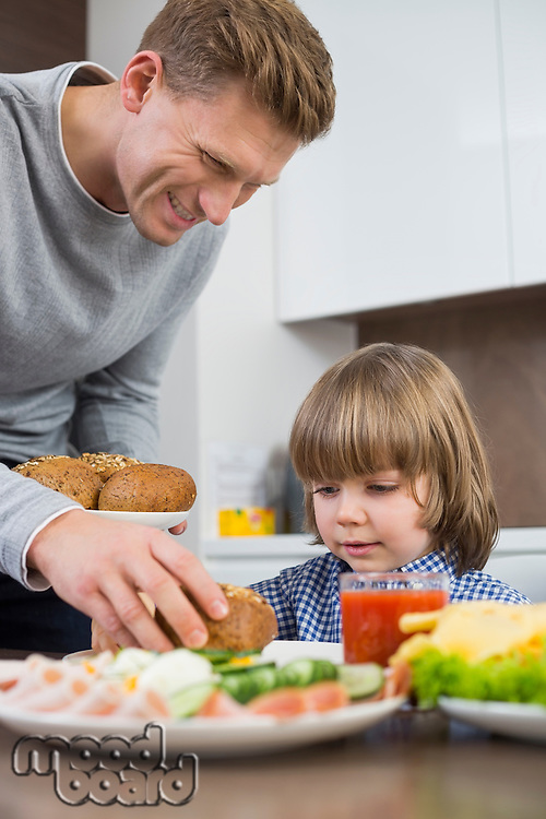 Happy father serving meal to son at table in kitchen