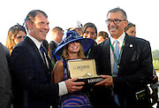Amy Figueroa, of Longines, presents owners Bobby Flay, left, and Kenny Troutt with a Longines timepiece after their horse Creator won the 148th Belmont Stakes, Saturday, June 11, 2016, at Belmont Park in Elmont, NY. Longines, the Swiss watchmaker known for its elegant timepieces, is the Official Watch and Timekeeper of the 148th running of the Belmont Stakes. (Diane Bondareff/AP Images for Longines)