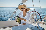 Mature woman on sailboat, reading a Magazine, Adriatic Sea, Croatia